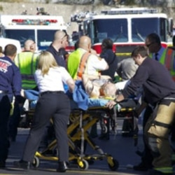 Emergency workers treat a victim of the shooting at a Tucson shopping center