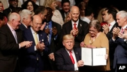 President Donald Trump shows the signed executive order surrounded by cabinet members and supporters in Miami, Friday, June 16, 2017
