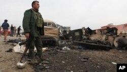Un combatiente kurdo monta guardia un área dañada por una bomba del grupo Estado islámico.