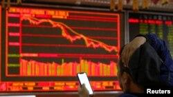 一名中國投資者坐在北京一個證券交易所的電子顯示屏前。(2018年10月11日)