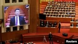 资料照:2019年中国政协会议开幕时,会场屏幕显示中国领导人习近平出席会议的图像