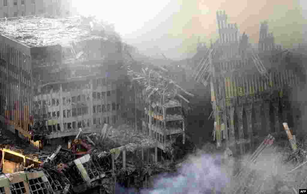 (FILE) Early morning light falls on the the debris and smoke of the World Trade Center twin towers collapse early 12 September, 2001 in New York City. Rescue efforts at the site are underway. Both towers of the World Trade Center collapsed after hijacked airliners collided with them 11 September. AFP PHOTO/Marcos TOWNSEND (Photo by MARCOS TOWNSEND / AFP)