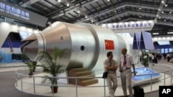 FILE - Visitors sit besides a model of China's Tiangong 1 space station at the 8th China International Aviation and Aerospace Exhibition in Zhuhai city, south China, in November 2010. Tiangong 2 will be sent into space Thursday.