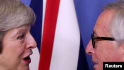 FILE - British Prime Minister Theresa May meets with European Commission President Jean-Claude Juncker to discuss Brexit, at the EU headquarters in Brussels, Dec. 11, 2018.