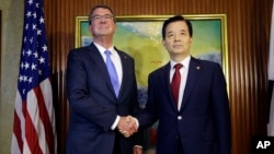 U.S. Defense Secretary Ash Carter, left, shakes hands with South Korea's Defense Minister Han Min Koo during their bilateral meeting on the sidelines of the 15th International Institute for Strategic Studies Shangri-la Dialogue, or IISS, Asia Security Summit in Singapore, June 4, 2016.