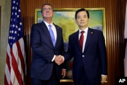 U.S. Defense Secretary Ash Carter, left, shakes hands with South Korea's Defense Minister Han Min Koo during their bilateral meeting on the sidelines of the 15th International Institute for Strategic Studies Shangri-la Dialogue, or IISS, Asia Security Sum
