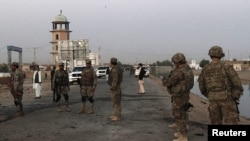 U.S. troops and Afghan security force arrive at the site of a suicide car bomb attack in Kandahar province. (file) Al-Harbi coordinates those who fight Coalition forces in Afghanistan.