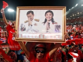 A red-shirted supporter holds up a pictures of Thailand's Prime Minister Yingluck Shinawatra and her brother Thaksin Shinawatra, during a rally at Rajamangala national stadium in Bangkok, Nov. 19, 2013.