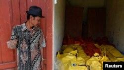 Một người địa phương ở Sukabumi đứng cạnh thi thể các thuyền nhân chết khi tàu của họ bị chìm ở ngoài khơi đảo Java, Indonesia, 28/9/2013.