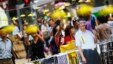People take pictures behind a cutout of Chinese President Xi Jinping on which pro-democracy protesters put goggles and a yellow ribbon, their symbols, in the part of Mongkok shopping district protesters are occupying in Hong Kong, Oct. 31, 2014.