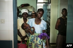 FILE - An HIV-positive mother holds her sick child at the Thyolo District hospital in Malawi, Nov. 26, 2014.