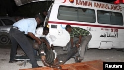Somali policemen move a victim after a suicide bomb attack at Village restaurant in Mogadishu, September 20, 2012.