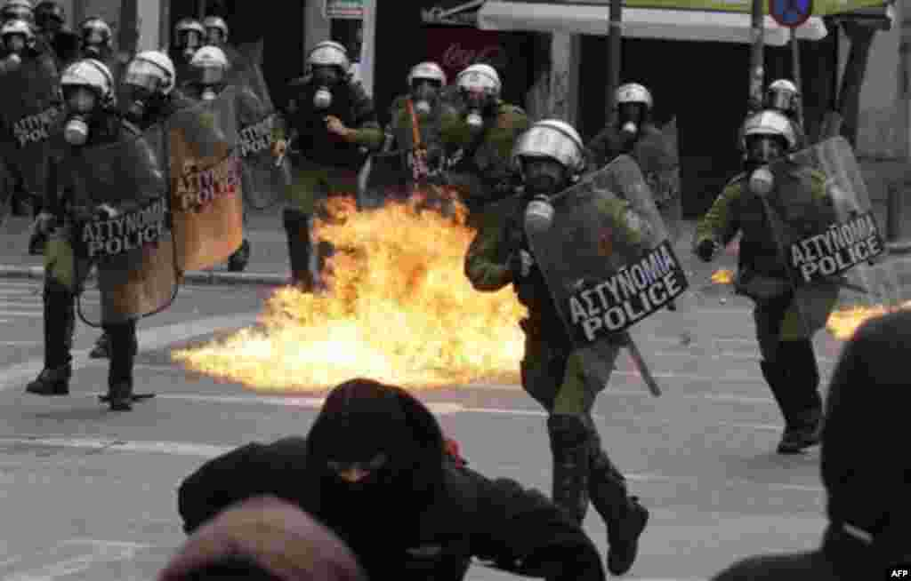A petrol bomb burns as Greek riot policemen clash with protesters in Athens, Wednesday, Feb. 23, 2011. Scores of youths hurled rocks and petrol bombs at riot police after clashes broke out Wednesday during a mass rally taking place as part of a general st