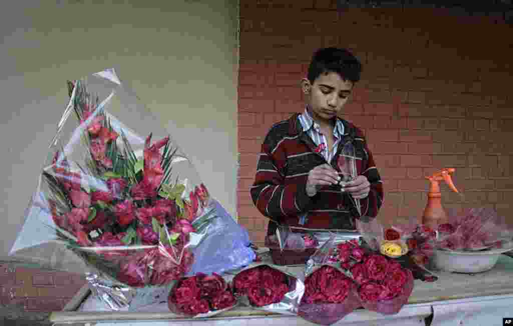 A boy prepares bouquets of flowers for sale on Valentine's Day while waiting for customers at a roadside stall in Faisalabad, Pakistan, February 14, 2012. (Reuters)