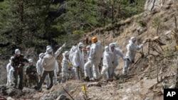 Les services de secours d'urgence français travaillent parmi les débris de l'avion de Germanwings sur le lieu de l'accident près de Seyne-les-Alpes, en France, le 3 Avril 2015. (AP Photo/Yves Malenfer, Ministere de l'Interieur)