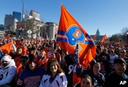Broncos fans cheer after arriving early to await the start of a victory rally to celebrate the Broncos' win over the Carolina Panthers in Super Bowl 50, in Denver, Feb. 9, 2016.