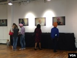 Sikh Coalition volunteers speak with visitors as they look at portraits from the Sikh Project. (E. Sarai/VOA)