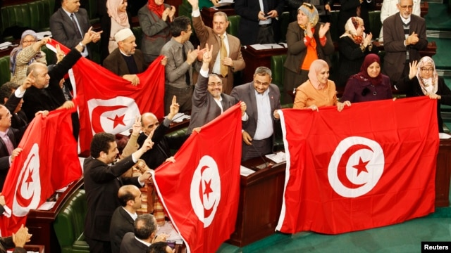Members of the Tunisian parliament wave flags after approving the country's new constitution in the assembly building in Tunis, Jan. 26, 2014.