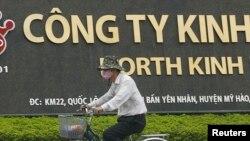 一位男士骑自行车路过河内城外兴安省越南京都集团的一家工厂。(资料照)