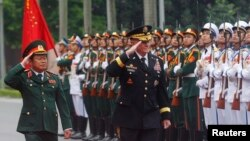 U.S. Chairman of the Joint Chiefs of Staff General Martin Dempsey (C) reviews the honor guard with his Vietnamese counterpart General Do Ba Ty in Hanoi August 14, 2014. REUTERS