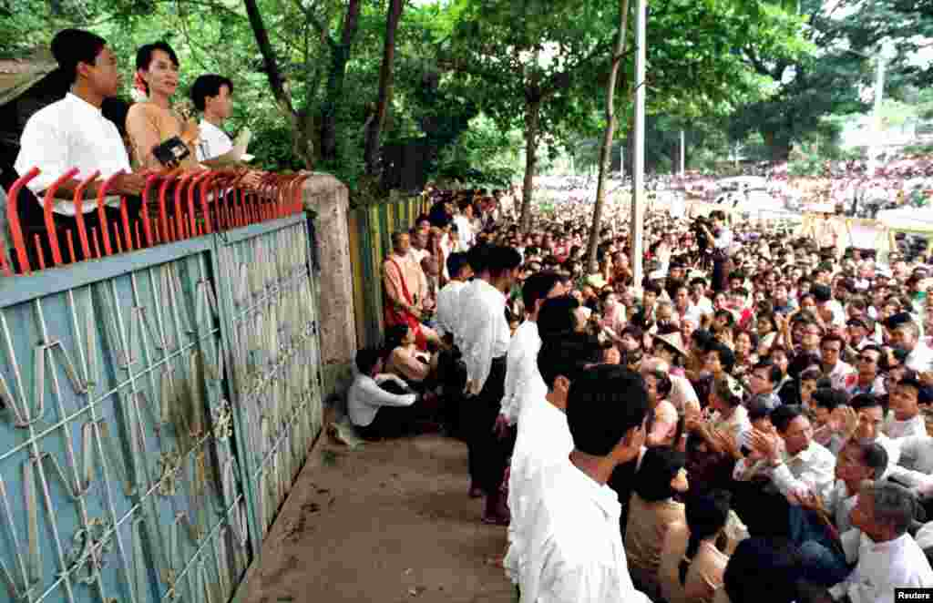 Aung San Suu Kyi addresses about 4,000 people gathered outside her house in Rangoon, Burma, June 1, 1996.