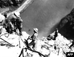 Workers drill into the canyon wall above the Colorado River