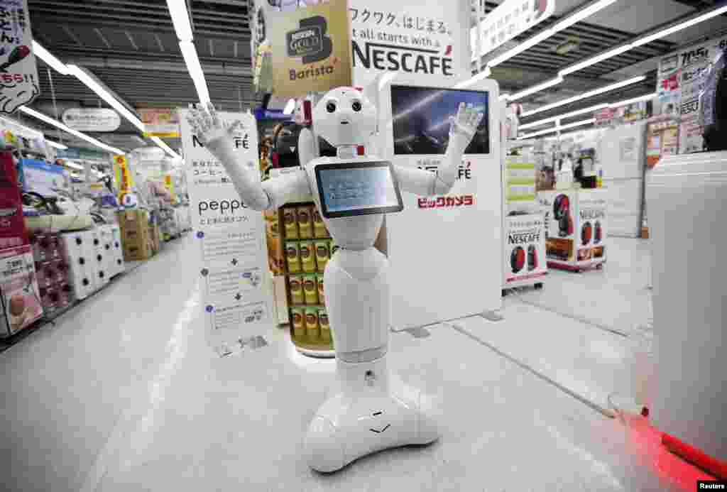"SoftBank Corp's human-like robot named ""Pepper"" introduces Nestle's coffee machines at an electronic shop in Tokyo, Japan."