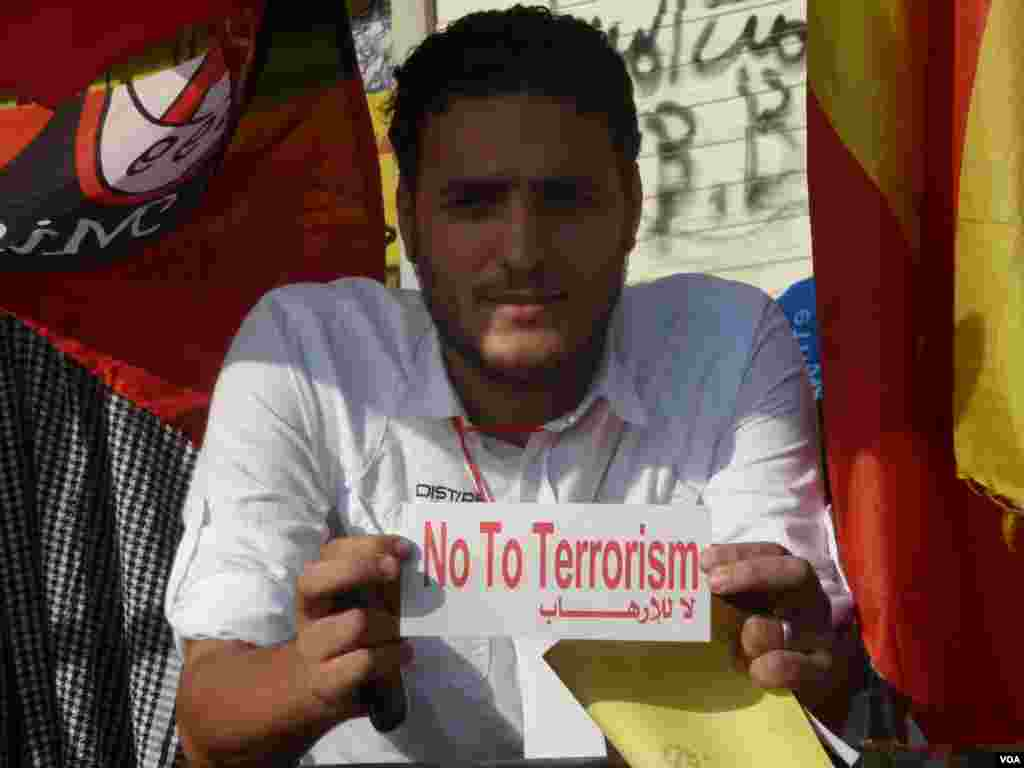 """A man in Tahrir Squareholds a sticker saying """"No To Terrorism"""" in reference to the Muslim Brotherhood, July 7, 2013. (S. Behn/VOA)"""