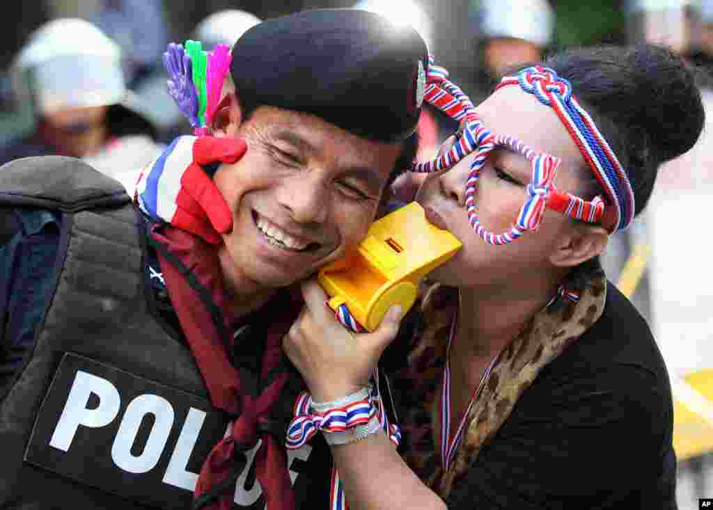 An anti-government protester blows a giant whistle to a riot police officer outside the headquarters of Prime Minister Yingluck Shinawatra's ruling Pheu Thai Party in Bangkok, Thailand.