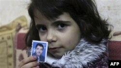 Трехлетняя Мария держит в руках фотографию своего отца, Дирара Абу Сиси. Бейт Лахия. Сектор Газа. 8 марта 2011 года