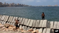 In this August 8, 2019, photo, workers prepare to place cement blocks to reinforce the sea wall against rising water levels on the corniche in Alexandria, Egypt. (AP Photo/Maya Alleruzzo)