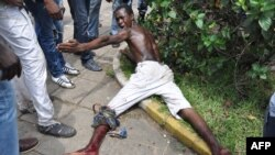 Injured man lies on ground after clash with police at market in Abobo neighborhood in Abidjan, Oct. 15, 2012.