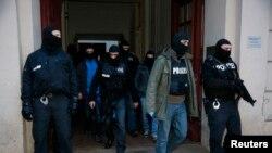 Polisi Jerman meninggalkan sebuah apartemen di Distrik Wedding Berlin (16/1). Sekitar 250 polisi dikerahkan dalam penggerebegan yang berhasil menangkap 2 terduga teroris.
