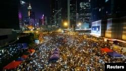 Para demonstran pro-demokrasi di Hongkong bernyanyi sambil melambaikan telepon genggam mereka dalam sebuah aksi protes di luar gedung pemerintah di Hong Kong (10/10).