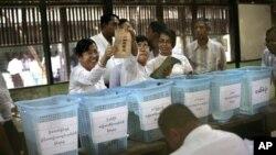 Para petugas pemilu sedang menghitung surat suara yang masuk di sebuah TPS di Yangon (Rangun), Burma (1/4).