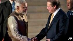 나렌드라 모디 인도 신임 총리(왼쪽)가 26일 자신의 취임식을 위해 뉴델리를 방문한 나와즈 샤리프 파키스탄 총리와 악수하고 있다.