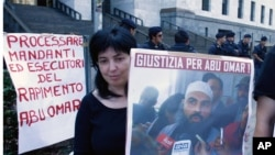 "A protester holding up a poster with writing reading in Italian ""Justice for Abu Omar"" above a picture of Muslim cleric Osama Moustafa Hassan Nasr, also known as Abu Omar, outside Milan's court house while the trial of 26 Americans and seven Italians accused of orchestrating a CIA-led kidnapping of an Egyptian terror suspect Nasr was taking place inside the courtroom, in Milan, Italy, Sept. 23, 2009. Italy's president on Friday, April 5, 2013 pardoned a U.S. Air Force colonel convicted in absentia by Italian courts in the CIA-conducted abduction of an Egyptian terror suspect from a Milan street in a move he hoped would keep American-Italian relations strong, especially on security matters."
