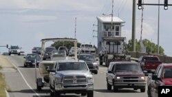 Numerosos automovilistas cruzan un puente levadizo en Wrightsville Beach, Carolina del Norte, mientras evacuan la zona ante la llegada del huracán Florence, el martes 11 de septiembre de 2018. (AP Foto/Chuck Burton)