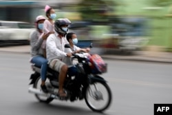 FILE - Members of a family wear face masks, as a preventive measure against the spread of the COVID-19 novel coronavirus, as they ride their motorcycle along a street in Phnom Penh on April 28, 2020.