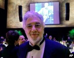 """El tenor Placido Domingo posa para una foto delante de una imagen suya en la juventud cantando en la ópera """"Otello"""" de Verdi. Abril 28 de 2019, en la Ópera Metropolitana de Nueva York."""
