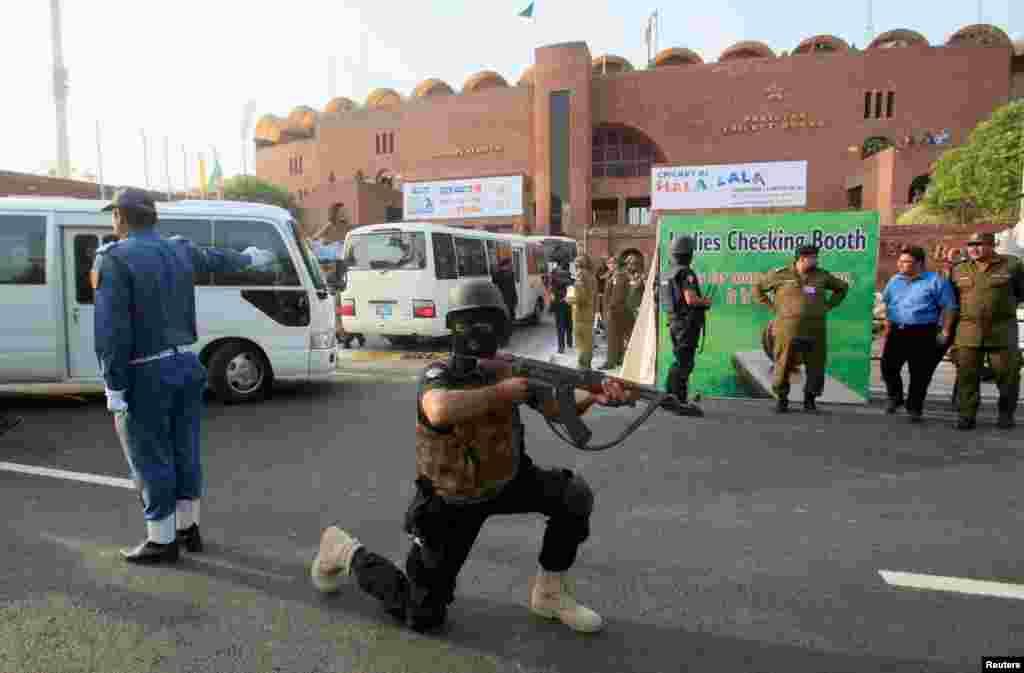 ورلڈ الیون کے کھلاڑیوں کی قذافی اسٹیڈیم آمد سے قبل ایک سکیورٹی اہلکار تربیتی مشق میں پوزیشن لیے ہوئے ہے