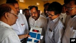 FILE - Indian election officials seal an electronic voting machine after the closing of a polling center in Kunwarpur village, Uttar Pradesh state, India.