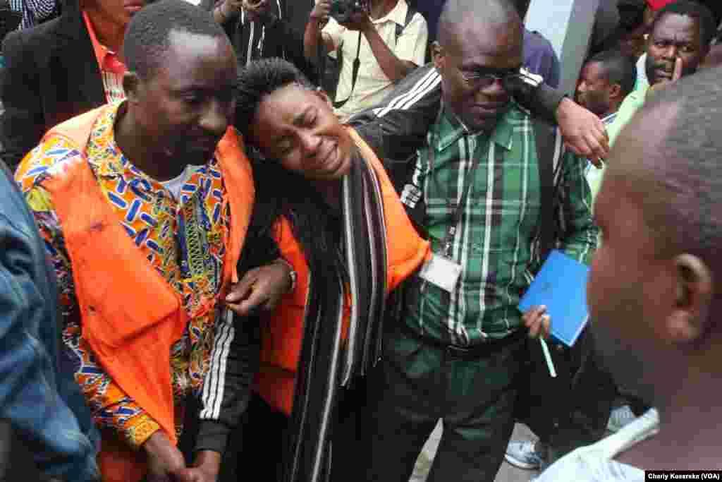 Un couple rescapé du naufrage, émotionné, est tenu par des secouristes lundi 30 novembre près de lac Kivu. VOA/Charly Kasereka.