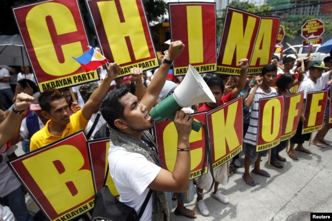 FILE - Filipinos chant anti-China slogans over the disputed Scarborough Shoal islands in the South China Sea claimed by both nations as they march toward the Chinese consulate in the Makati financial district of Manila, Philippines, May 11, 2012.