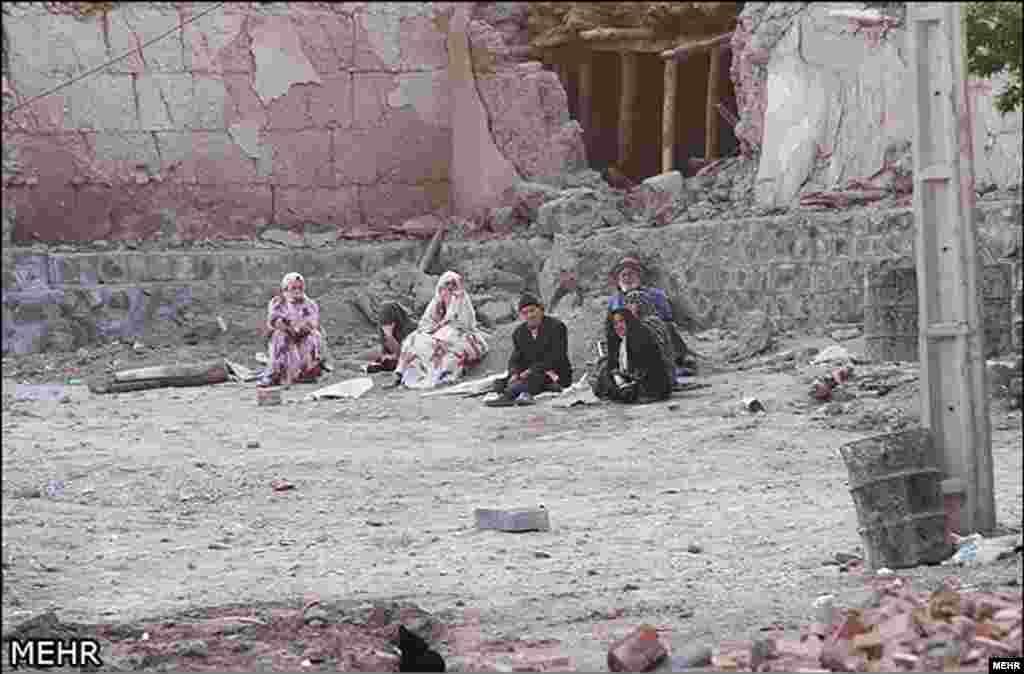 伊朗西北部受到地震破壞村鎮的災民在損毀的家園外面等候救助