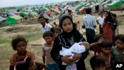 An internally displaced Rohingya woman holds her newborn baby surrounded by children in the foreground of makeshift tents at a camp for Rohingya people in Sittwe, northwestern Rakhine State, Burma, May13, 2013.
