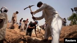 FILE - Members of the Ahmadiyya Muslim community dig graves for victims in Chenab Nagar, in Punjab's Chiniot district, about 200 km (124 miles) northwest of Lahore, May 29, 2010. Gunmen attacked Ahmadiyya worshippers in two Lahore mosques the day before, taking hostages and killing at least 70 people, officials said.