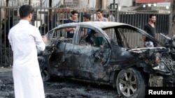 Warga melihat lokasi serangan bom mobil di Baghdad (18/9). (Reuters/Thaier Al-Sudani)