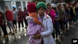 Maria del Carmen Mejia holds her daughter Britany Sofia while standing a line outside a migrant shelter in Tijuana, Mexico, Thursday, Nov. 22, 2018.