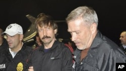 This image provided by the Drug Enforcement Administration shows Russian arms trafficking suspect Viktor Bout, center, in U.S. custody after being flown from Bangkok to New York, 16 Nov 2010
